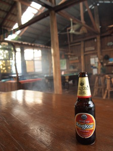 A beer bottle on a table in a jungle lodge