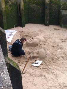 A man sculpting faces in the sand by the Thames