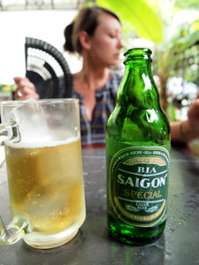 A bottle and glass of Saigon beer on a table in front of of a woman with a fan.